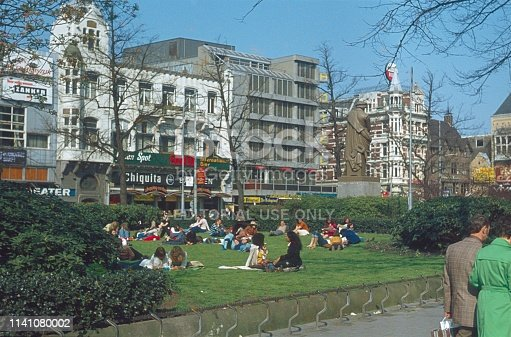 Rembrandtplein, Amsterdam, Netherlands, 1974. Young people are sitting on a meadow at Rembrandtplein on a sunny day. Also: buildings, shops, billboards, passers-by and the Rembrandt Monument.