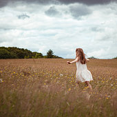A little girl is running in a meadow before a storm
