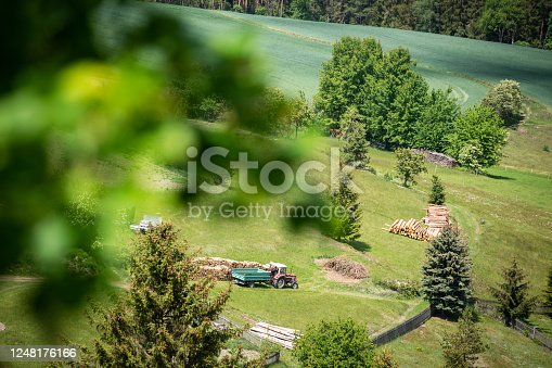 Thuringia, Germany: Top view of a meadow with a tractor and stacked wood in the Thuringian forest.