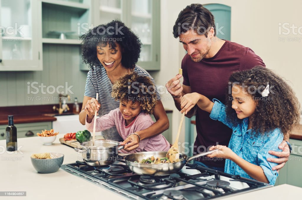 A meal cooked by the whole family tastes better - Foto stock royalty-free di Adulto