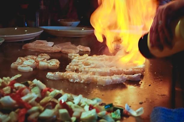 zubereitete speisen vor gäste im teppanyaki-restaurant - teppan yaki grill stock-fotos und bilder