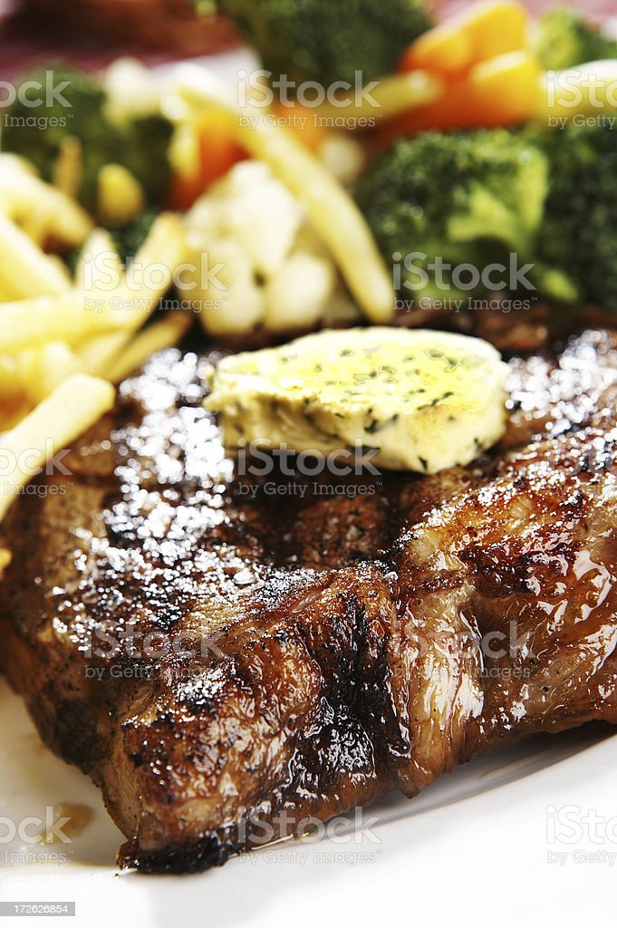 Meal of grilled steak with butter and vegetables royalty-free stock photo