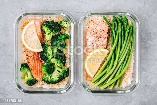 Meal prep lunch box containers with grilled salmon fish, rice, green broccoli and asparagus