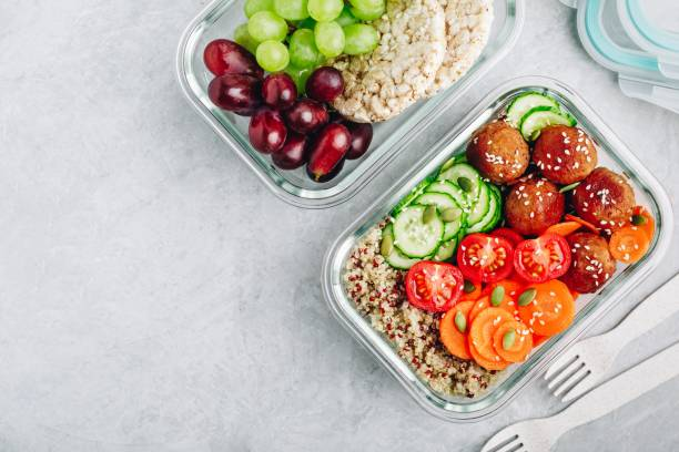 Meal prep lunch box containers with quinoa, meatballs cucumbers, carrots and pumpkin seeds stock photo