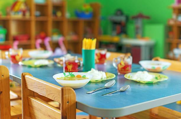Meal time in kindergarten. stock photo