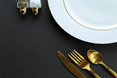 Elegant white, gold and black table setting. Copy space.