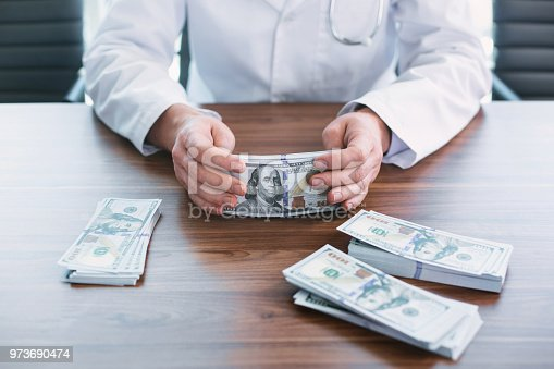 182362845 istock photo Mean doctor taking bribes in his office 973690474