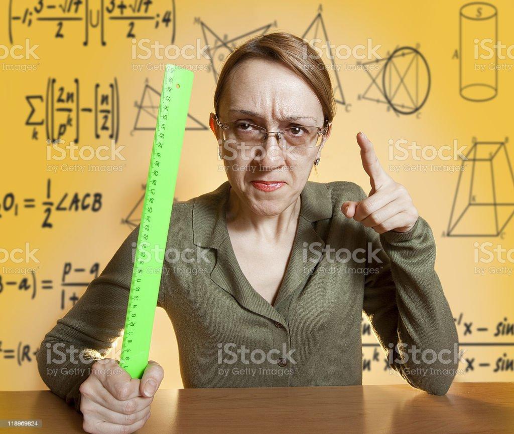 Mean female teacher holding ruler and pointing her finger stock photo
