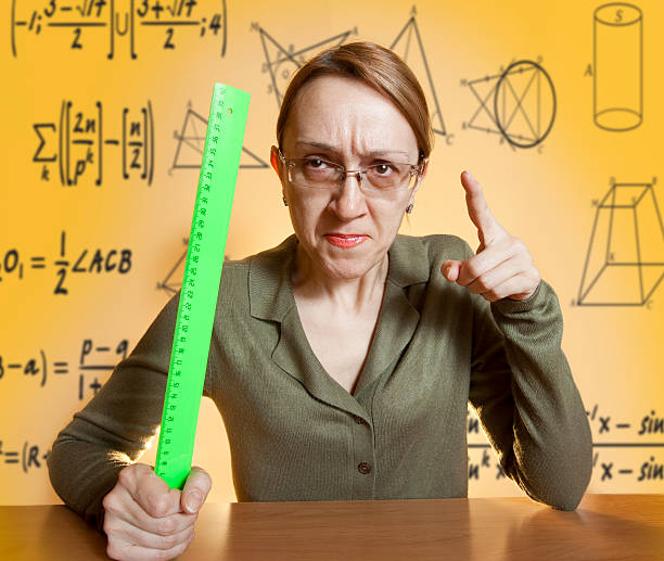 Mean female teacher holding ruler and pointing her finger Crazy female teacher cruel stock pictures, royalty-free photos & images