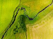 Meander river  with tree along side, shore, trough a farming landscape