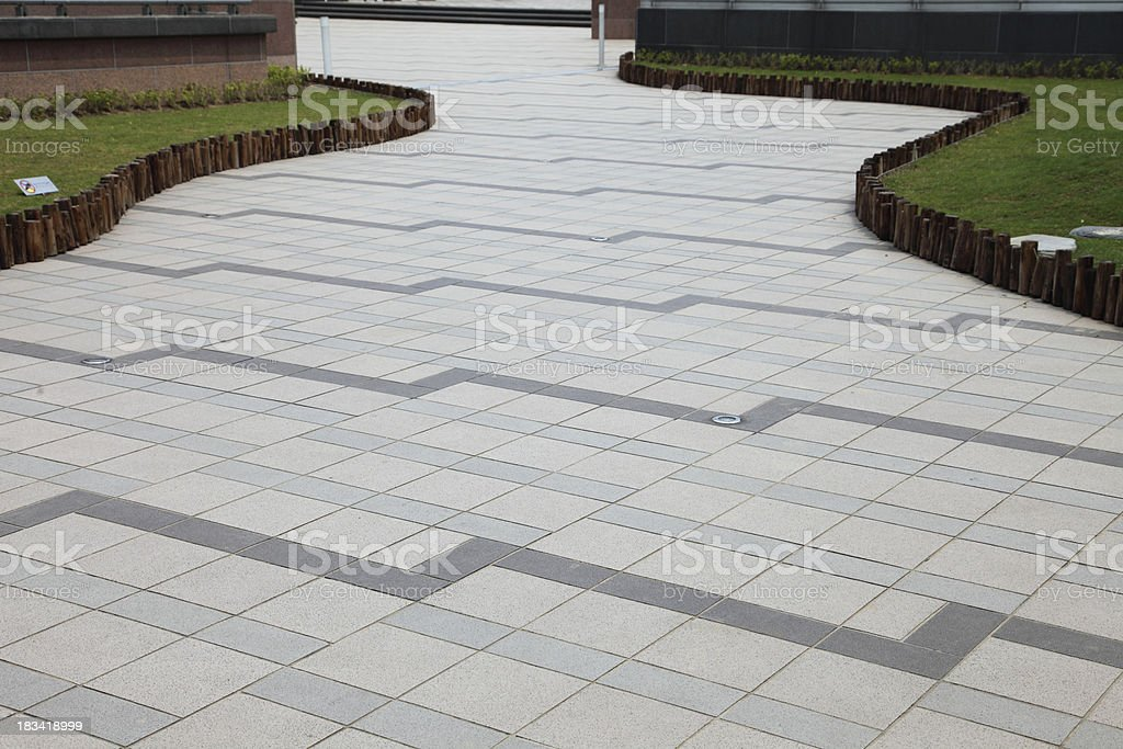 Meandering paved path between grass royalty-free stock photo