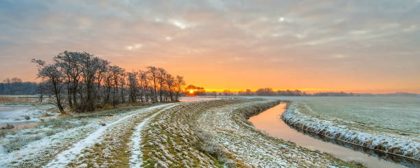 meandering river in frozen grassland landscape - february stock photos and pictures