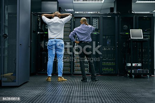 Rearview shot of two IT technicians having difficulty repairing a computer in a data center