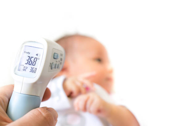 Measure baby's fever with digital fever meter. sick baby with high fever stock photo