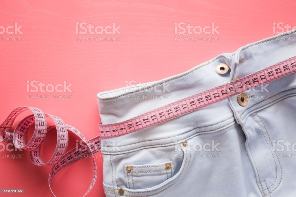 Measure tape with light blue jeans on the pastel pink background. Women diet. Mock up for healthy lifestyle, body slimming, weight loss or dressmaker's offer or other ideas. Empty place for text. stock photo