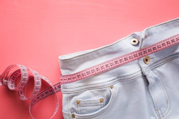 meten tape met lichte spijkerbroek op de pastel roze achtergrond. vrouwen dieet. bespotten voor gezonde levensstijl, lichaam vermageren, gewichtsverlies of naaister de aanbieding of andere ideeën. lege ruimte voor tekst. - te groot stockfoto's en -beelden