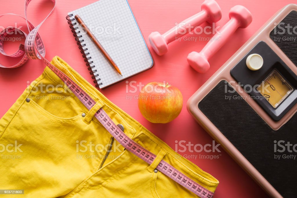Measure tape with yellow jeans, dumbbells, weight scale, apple, notebook on a pink background. Women diet before summer season. Healthy lifestyle, body slimming, weight loss concept. Cares about body. stock photo