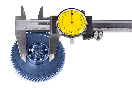 Silvery measuring tool with round yellow dial and black pointer. Vernier scale. Cogwheel and ball bearing. Involute, cycloid. Blue metal part. Quality control