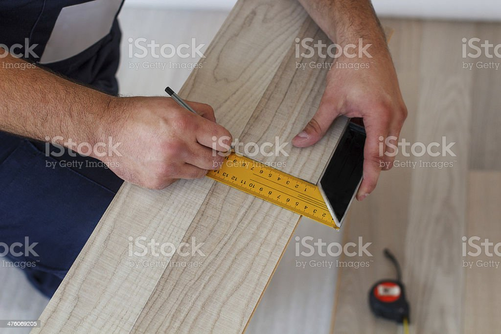 Measuring and laying laminate flooring in a home. royalty-free stock photo
