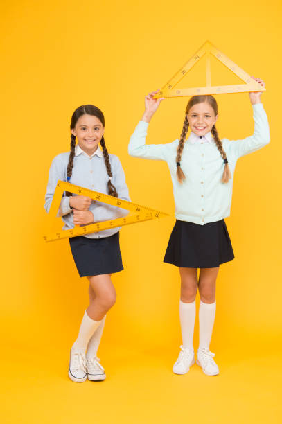 Measuring angles at geometry. Cute schoolgirls holding triangles for geometry lesson on yellow background. Little girls learning geometry. Small children with geometrical tools for geometry stock photo