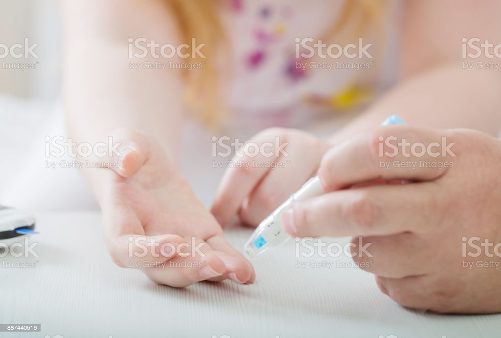 Measuring Blood Sugar Level Of Teen Girl With Glucometer stock photo