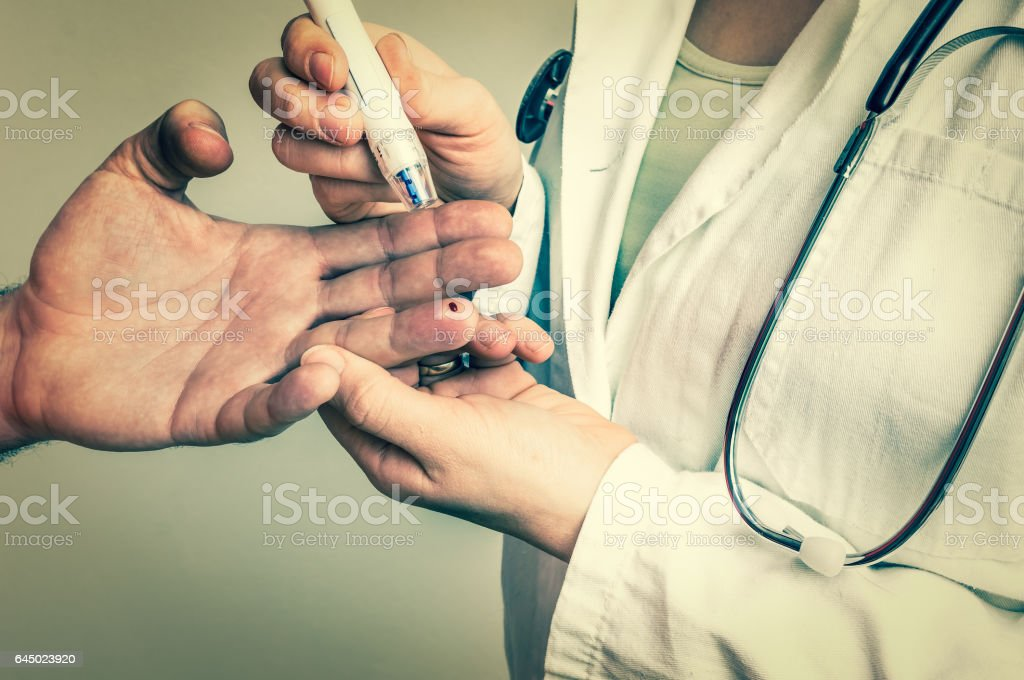 Measuring blood sugar on finger - diabetes concept stock photo