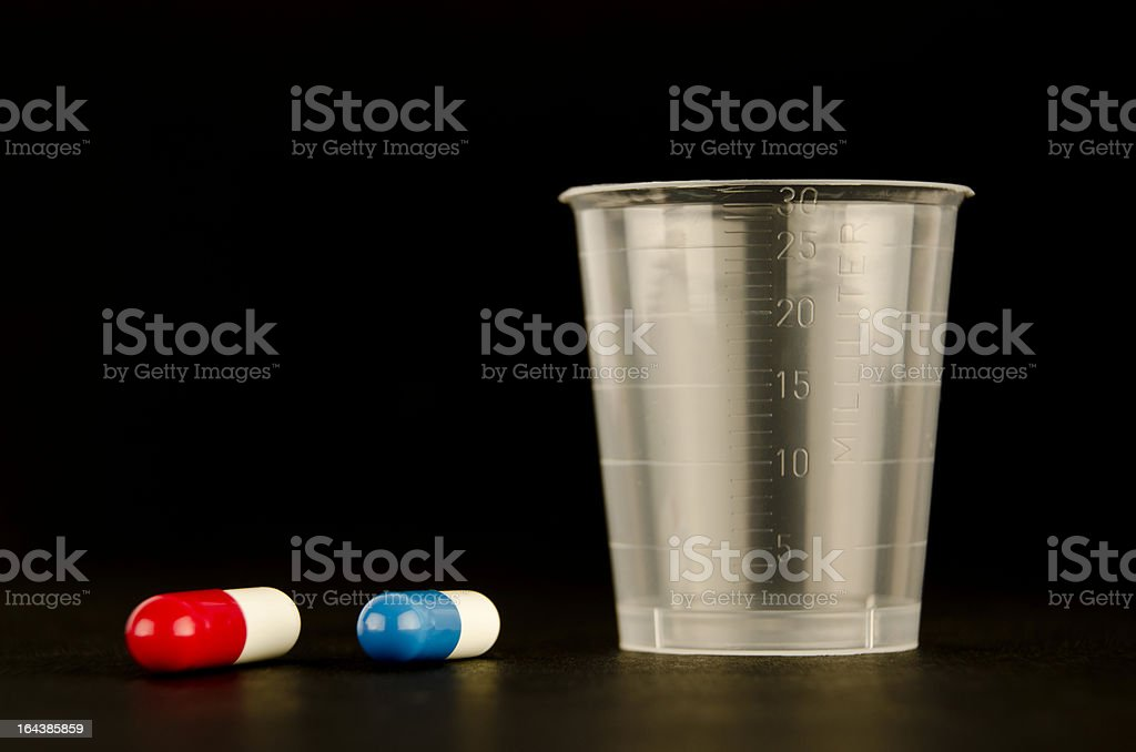 Measuring cup and two pills stock photo