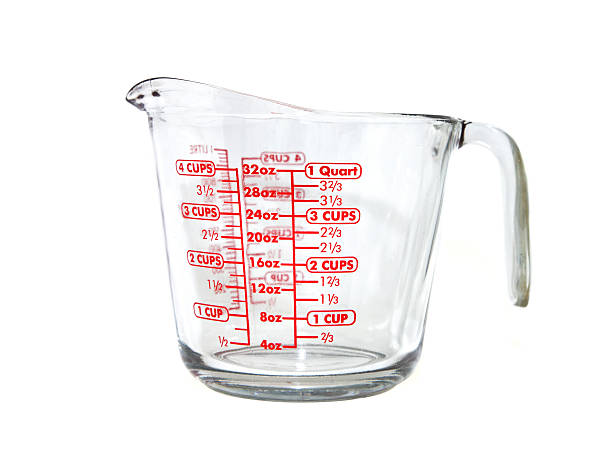Measuring Cup A large glass measuring cup with measurements on the side in red, photographed against a white background. dry measure stock pictures, royalty-free photos & images