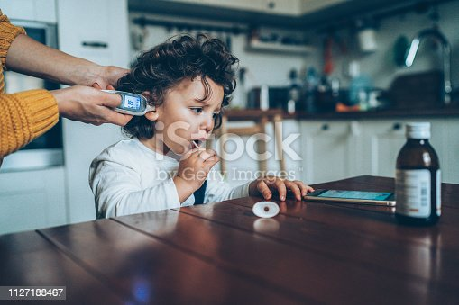 Mother with ear thermometer checking temperature