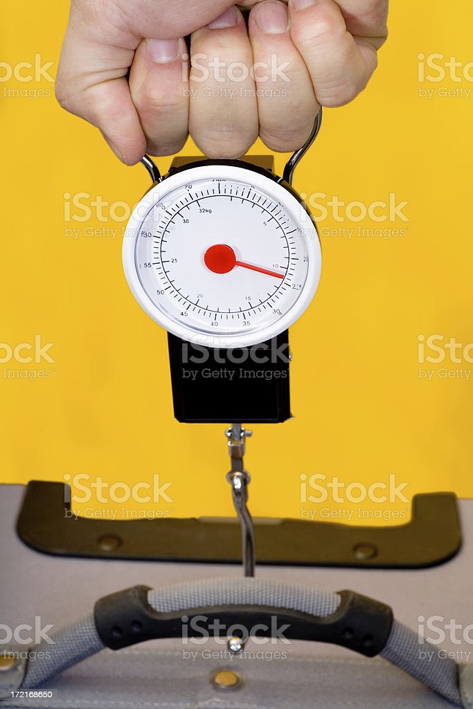 Measuring luggage with a hand scale. stock photo