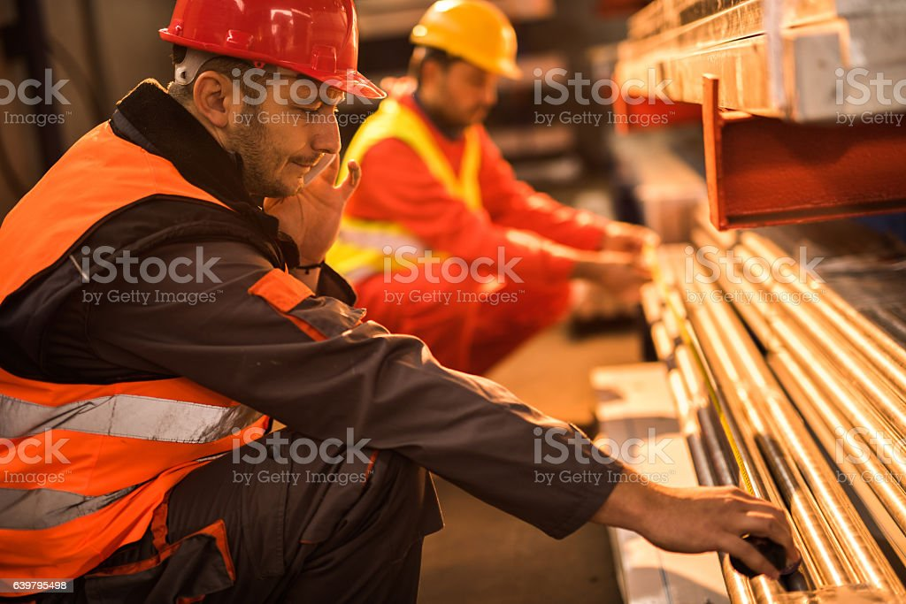 Measuring metal tubes while talking on cell phone! stock photo