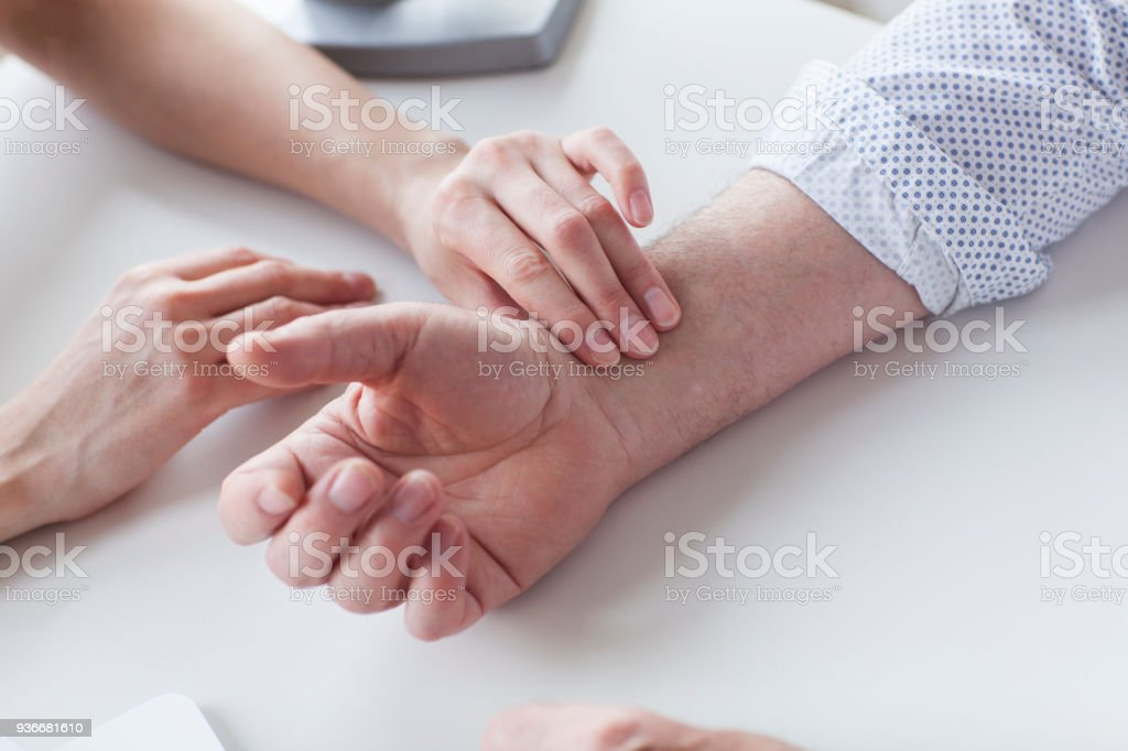 Measuring of pulse on wrist by the doctor. Feamle docotr is examining a patient. A Helping Hand Stock Photo