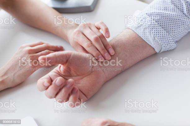 Measuring Of Pulse On Wrist By The Doctor Stock Photo - Download Image Now