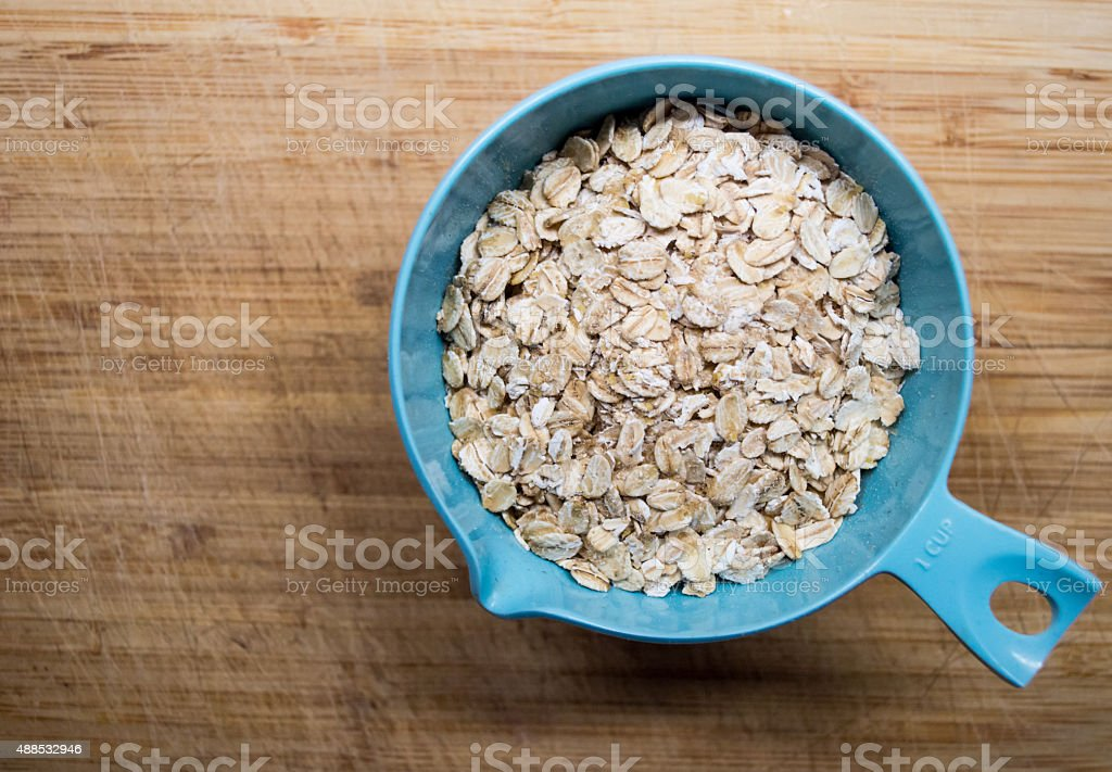 Measuring One Cup of Traditional Jumbo Rolled Oats Overhead View stock photo
