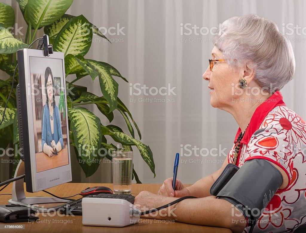 Measuring pressure during virtual doctor visit stock photo