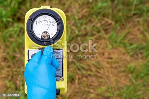 A blue gloved hand holds a radiation meter. The meter shows a high level of radiation. Grass in the background, most of which is brown and dead.