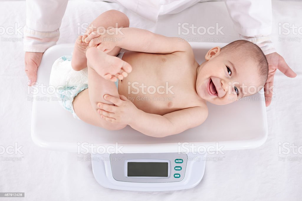 Measuring smiling beautiful comfortable little baby stock photo