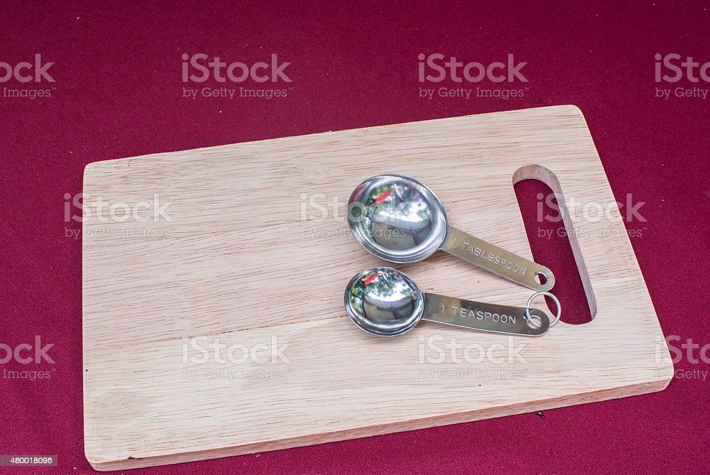 Measuring spoons on chop block stock photo