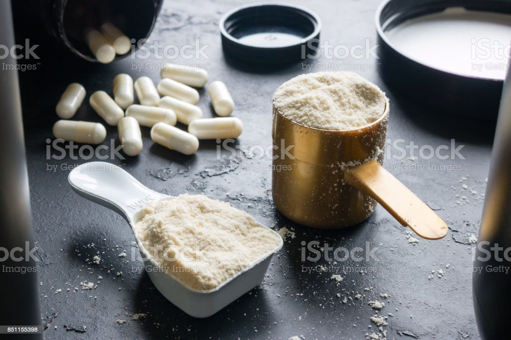 measuring spoons with sports supplements on a black background stock photo