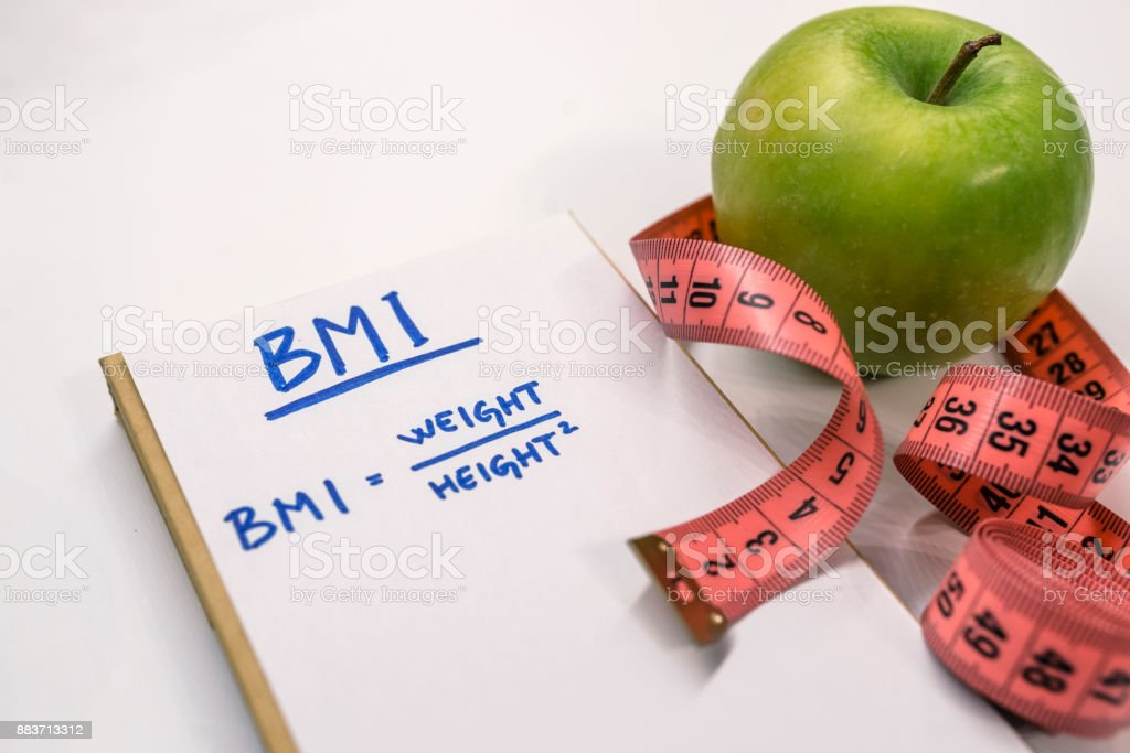 Measuring tape, a marker and a notepad with a Body mass index formula. stock photo