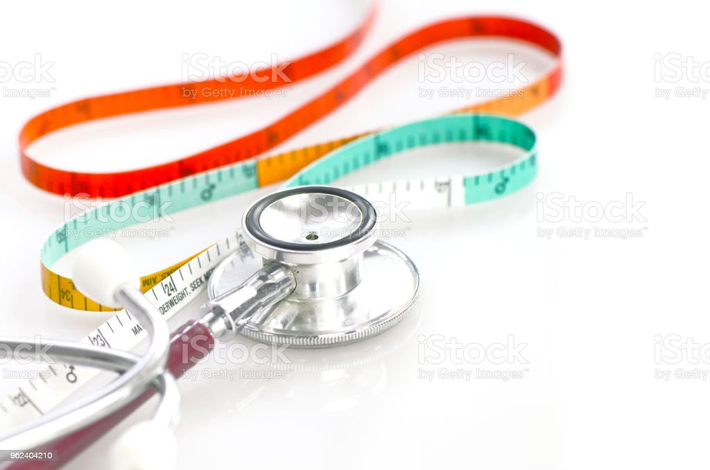 Measuring tape and stethoscope in weight and waist control concept. stock photo