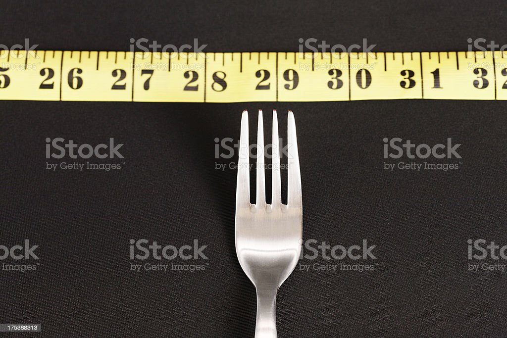 Measuring tape laid along top of fork: watch your diet! stock photo