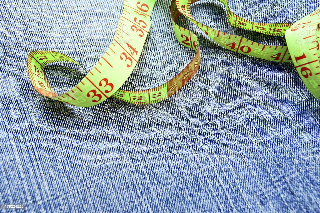 Measuring tape on a fabric (jeans). royalty-free stock photo