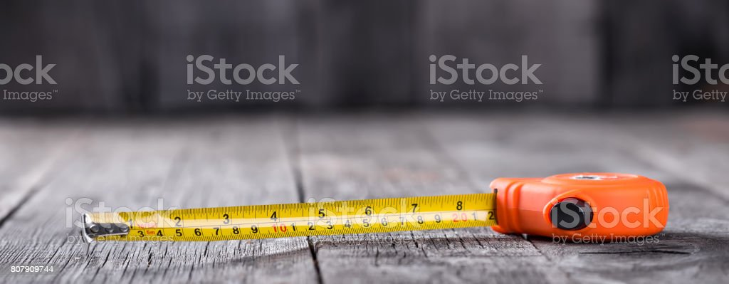 Measuring tape on a wooden board stock photo
