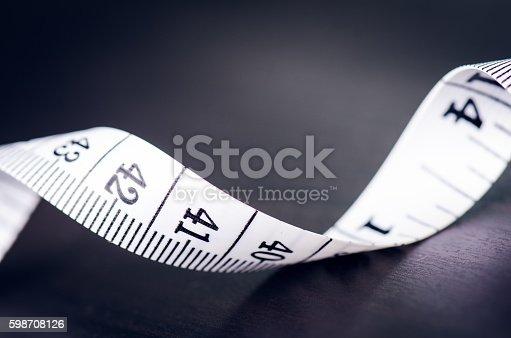 istock Measuring tape on dark background 598708126