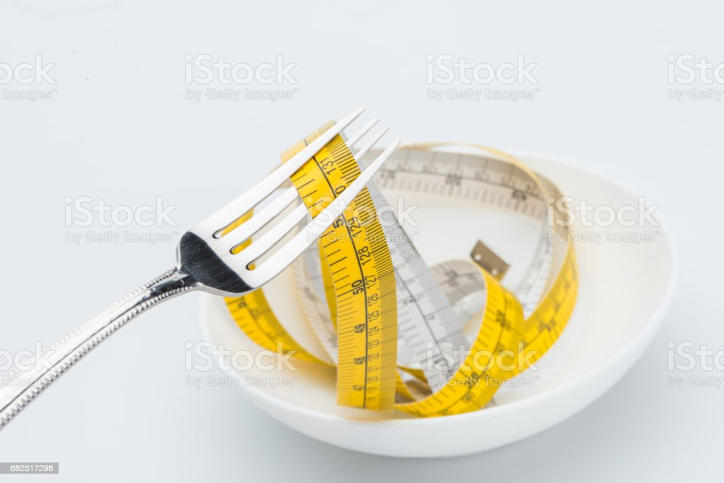 measuring tape on fork isolated on white, healthy living concept Lizenzfreies stock-foto