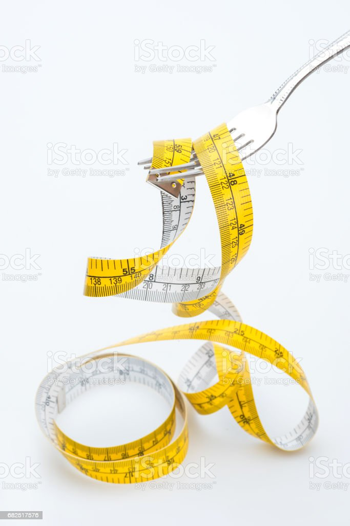 measuring tape on fork isolated on white, healthy living concept royalty-free stock photo