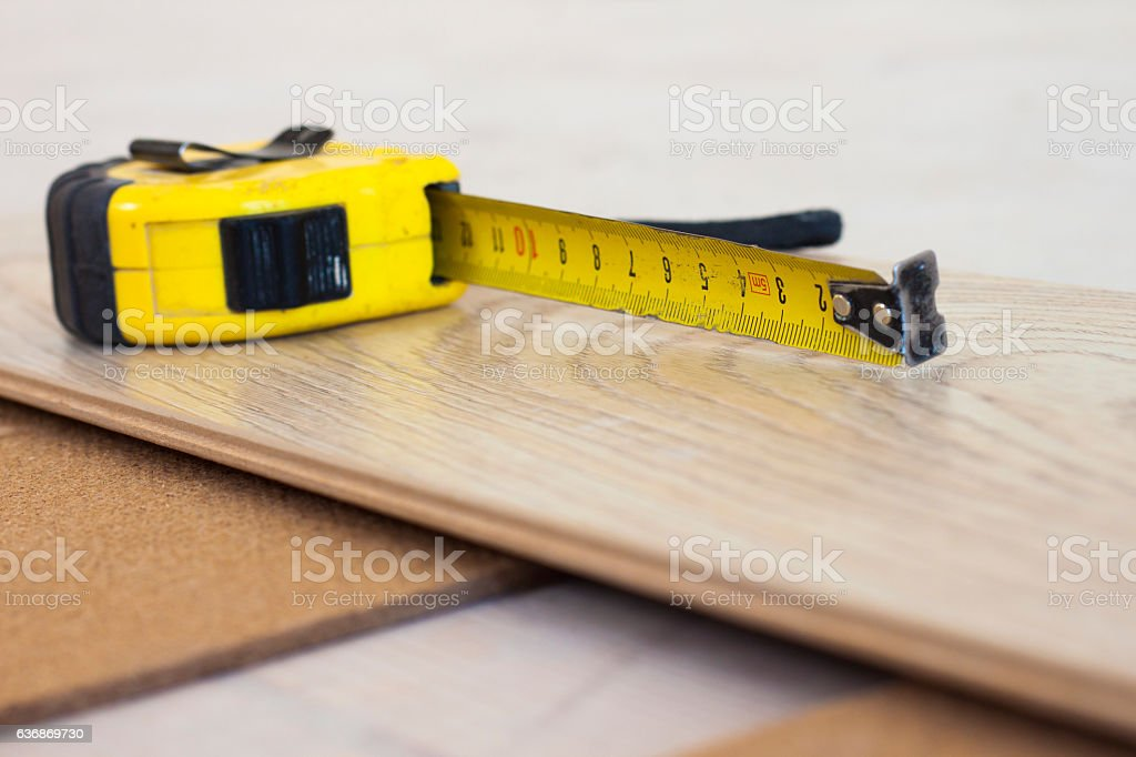 Measuring tape on laminate floor plank stock photo