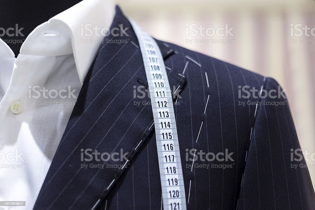 A measuring tape on top of a mans suit stock photo
