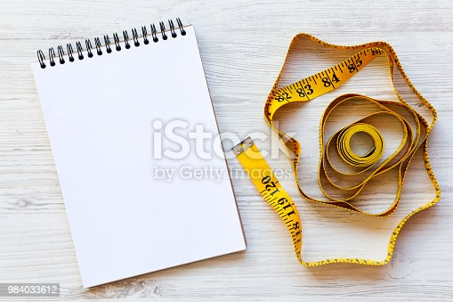 istock Measuring tape with notepad on a  white wooden surface, from above. Flat lay, top view. Copy space. Dieting concept. 984033612